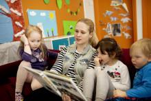 Aikuinen ja lapset sohvalla kirjaa lukemassa