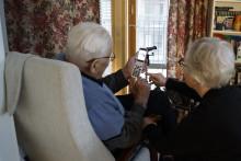 Vapaaehtoinen digiluotsi neuvomassa puhelimen käyttöä asiakkaan kotona