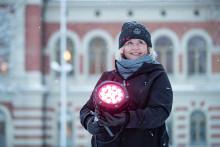 Nainen pitää punaista lamppua sylissään, taustalla kaupungintalo.