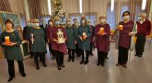 Harjun Laulu -kuoron laulajia seisomassa kynttilöitä käsissään