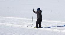 Lapsi hiihtää järven jäällä.