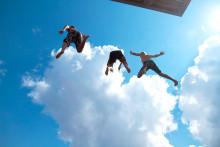 Pojat hyppäävät uimahyppytornista.