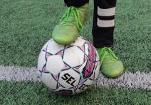 Jalka jalkapallon päällä tekonurmella.