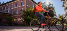 Opiskelijat pyöräilevät kampuksella