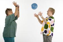 Kaksi naista heittämässä palloa valkokankaan edessä