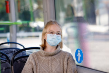 Nainen maski kasvoillaan linja-autossa.
