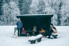 Nuori nainen ja mies sekä kaksi koiraa viettävät talvipäivää laavulla, nuotion ääressä.