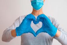 Hoitaja sormet sydämen muotoisessa asennossa.