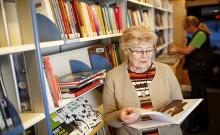 Asiakas selaa kirjaa kirjastoautossa