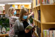 Maskit naamalla kirjaston hyllyjen välissä