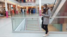 Nainen nojaa kaiteeseen ostoskeskuksessa. Hänellä on kasvomaski ja hän selaa puhelintaan.