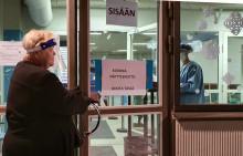 Asiakas visiirimaski yllään avaa ovea Killerin koronanäytteenottopisteellä.