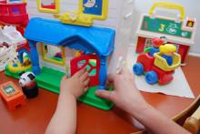 Lapsi ja aikuinen leikkivät lelutalolla.