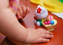Lelulla leikkivän lapsen kädet