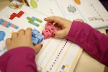 Lapsen kädet leikkivät legopalikoilla