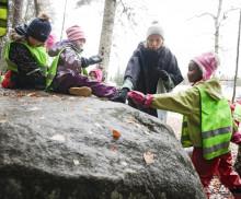 Lapset istuvat ison kiven päällä metsässä