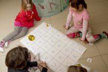 Lapset istuvat lattialla ja pelaavat lautapeliä