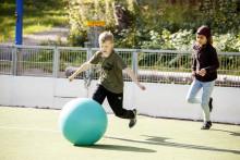 Lapset juoksevat kentällä pallon perässä