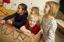 Lapset leikkivät pahvilaatikkoveneessä