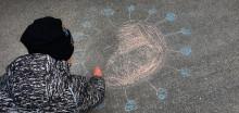 Lapsi piirtää liiduilla koronavirusta asfalttiin