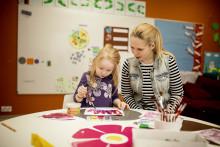 Lapsi ja aikuinen pöydän ääressä ja lapsi maalaa vesiväreillä / Hanna-Kaisa Hämäläinen