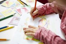 Lapsi piirtää ja värittää puuväreillä.