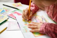 Lapsi värittää puuväreillä.