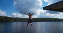 Poika hyppää uimaan