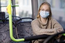 Kasvomaskia käyttävä tyttö linja-autossa