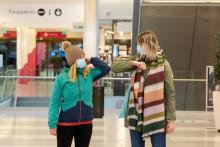 Kaksi naista maskit kasvoillaan ostoskeskuksessa.