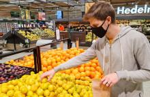 Mies poimii hedelmiä kaupassa kangasmaski kasvoillaan