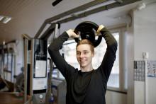 Mies kuntosalilla treenaamassa levypaino pään päällä