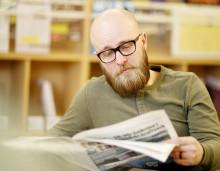 Mies lukee sanomalehteä