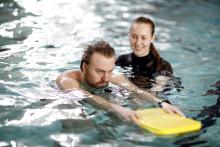 Mies uimassa laudan ja avustajan kanssa