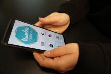 Henkilö pitelee käsissään puhelinta, jossa on auki Nuorten Jyväskylä -mobiilisovellus.
