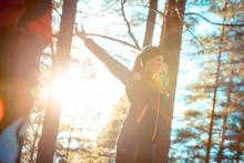Nainen venyttelee luonnossa auringonpaisteessa.