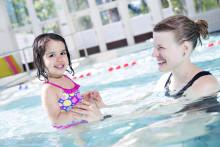 Nainen ja tyttö uimassa uimahallissa