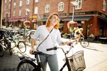 Nainen polkupyörän kanssa keskustassa