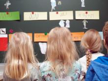 Neljä lasta katsoo taululta tehtäviä / Dolly Aittanen
