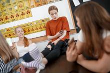 Neljä tyttöä istuu koulun käytävällä
