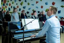 Niko Saloheimo vetää yhteislaulutilaisuutta pianon ääressä