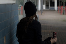 Nuori katsoo pois kamerasta, energiajuomatölkki kädessään
