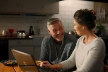 Keski-ikäinen pariskunta tietokoneen ääressä.
