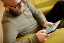 Mies selaa verkkokirjastoa tabletilla