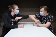 nuoret miehet kopauttavat kyynärpäitään ja pitävät maskeja kasvoillaan