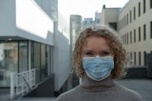 Nuori nainen katsoo kameraan kaupunkimaisemassa, maski kasvoilla
