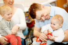 Perhe on neuvolassa. Leikki-ikäinen katsoo isä sylissä olevaa vauvaa.