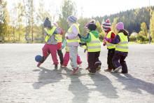 Pienet lapset ryhmässä palloleikeissä heijastinliivit päällä.
