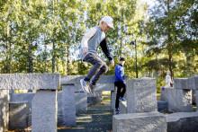 Poika ja mies liikkumassa Kangaslammen parkourpuistossa