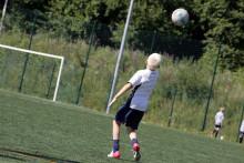 poika pelaa jalkapalloa nurmikentällä